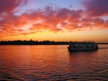 Туристическое судно на нолях реки на заходе солнца Стоковые Изображения