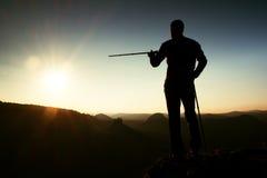 Туристская выставка гида правый путь с поляком в руке Hiker с sporty стойкой рюкзака на скалистой точке зрения выше туманная доли Стоковое фото RF