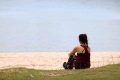 Туристская девушка ослабляя на пляже наслаждается видом на океан Стоковое Фото