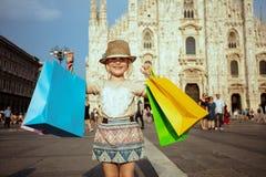 Туристская девушка перед Duomo показывая красочные хозяйственные сумки стоковые фото
