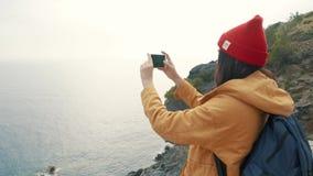Туристская девушка с положением рюкзака на краю фото скалы и стрельбы акции видеоматериалы