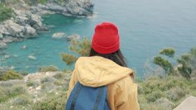 Туристская девушка с рюкзаком идет к лагуне наслаждаясь красивым видом сток-видео