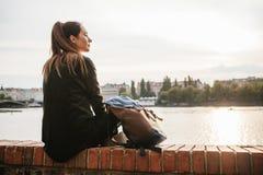 Туристская девушка с рюкзаком сидит рядом с рекой на предпосылке домов в Праге в чехии Стоковая Фотография