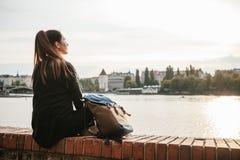 Туристская девушка с рюкзаком сидит рядом с рекой на предпосылке домов в Праге в чехии Стоковое фото RF