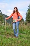 Туристская девушка hiker с красными волосами и рюкзаком счастливое положение в лесе горы с идя ручкой стоковое изображение