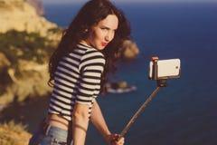 Туристская девушка делая фото selfie с ручкой на верхней части горы Стоковое Изображение RF