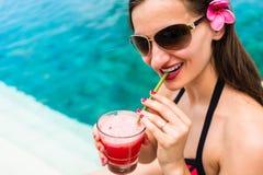 Туристская женщина в коктеиле красного бикини выпивая на пляже Стоковая Фотография