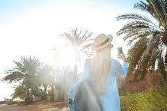 Туристская женщина в шляпе принимая фото старой части Дубай используя стоковое фото