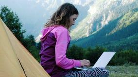 Туристская женщина использует ноутбук в природе, фрилансере печатая на компьютере около шатра в путешествии против фона  акции видеоматериалы
