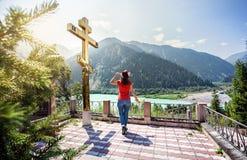 Туристская женщина на горах приближает к золотому кресту стоковое фото