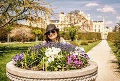 Туристская женщина представляя с flowerbed с замком Lednice, чехословакским Стоковое фото RF