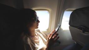 Туристская женщина сидя около окна самолета на заходе солнца и используя мобильный телефон во время полета Стоковое Фото