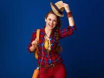 Туристская женщина с наушниками слушая к музыке и поднимая шляпе Стоковые Изображения RF