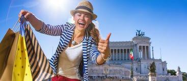 Туристская женщина с хозяйственными сумками в Риме показывая большие пальцы руки вверх стоковое изображение