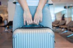 Туристская женщина с чемоданом ждать в аэропорте Концепция полета воздуха стоковое фото