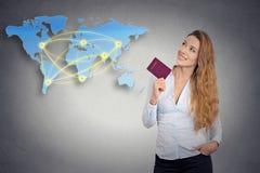Туристская молодая женщина держа пасспорт стоя смотрящ карту мира стоковое изображение rf