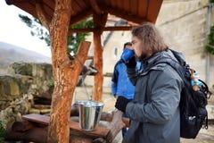 Туристская питьевая вода от хорошо монастыря Motsameta расположенного на захватывающем вершин скал мысе над загибом Tskha Стоковые Фотографии RF