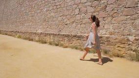 Туристская прогулка вдоль высокой стены замка, взгляд женщины на каменной кладке, Барселоне, Испании акции видеоматериалы