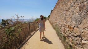 Туристская прогулка женщины вдоль высокой стены замка, наслаждается панорамой моря, Барселоной сток-видео