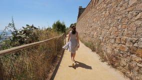Туристская прогулка женщины вдоль стены замка на холме Montjuic, Барселоне акции видеоматериалы