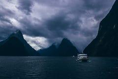 Туристская шлюпка плавая около гор на пасмурный день стоковое изображение