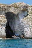 Туристская шлюпка входя в пещеру моря стоковая фотография rf