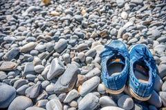 Туристские левые голубые тапки на каменном пляже и пошли поплавать в море стоковые фотографии rf
