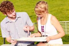 Туристские пары в городе прочитали карту Стоковая Фотография