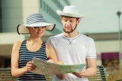 Туристские пары в городе смотря вверх направления на карте Стоковая Фотография RF