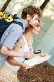 Туристские пары в городе смотря вверх направления на карте Стоковая Фотография