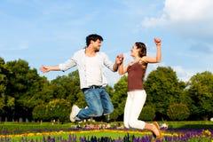 Туристские пары в городе паркуют скакать в солнце стоковые фотографии rf