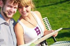 Туристские пары в городе прочитали карту Стоковое Фото
