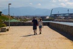 Туристские пары идя на прибрежную дорогу ираклиона Крита стоковая фотография rf