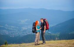 Туристские пары с рюкзаками на дороге в горах Стоковое фото RF