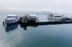 Туристские шлюпки паркуя на мирной воде и причаленные к плавучим докам пристани Shuishe на озере Солнц-лун на туманном утре в Na стоковые изображения