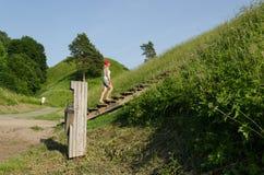 Туристские strairs подъема девушки на холме насыпи Стоковое Фото