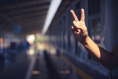 Туристский показывая знак руки мира на поезде стоковая фотография