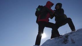 Туристский помогая подъем товарища по команде, человек с рюкзаком достиг вне руку помощи к его другу E сток-видео