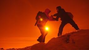 Туристский помогая подъем товарища по команде, человек с рюкзаком достиг вне руку помощи к его другу E акции видеоматериалы
