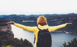 Туристский путешественник при рюкзак стоя с поднятыми руками на верхней части на горе, взгляде hiker девушки от задний смотреть н Стоковые Фото