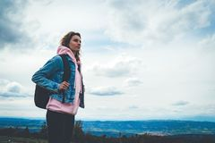 Туристский путешественник с черным рюкзаком на горе предпосылки, hiker смотрит вверх на облаках голубого неба, девушке наслаждаяс стоковое изображение