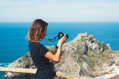 Туристский фотограф путешественника делая scape моря изображений на камере фото на gaztelugatxe океана предпосылки шагает на Испа стоковая фотография