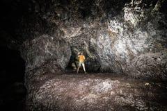 Туристский человек исследовать пещеру лавы с электрофонарем в Мауи, Гаваи стоковое фото rf