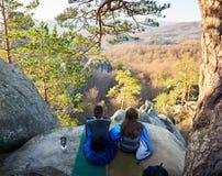 Туристский человек и девушка сидя в спальных мешках на большой горе трясут Стоковое Изображение RF