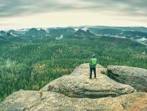 Туристский человек на крае утеса и смотреть вне в расстояние стоковое фото rf