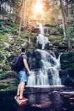 Туристский человек стоя близко водопад в горах и наслаждаясь взглядом стоковая фотография rf