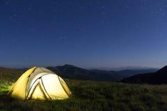 Туристский шатер hikers в горах на ноче с звездами в небе Стоковое Изображение