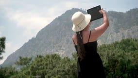 Туристское положение девушки около небольшого зеленого леса и высокого холма, держа устройство и фотографируя акции видеоматериалы