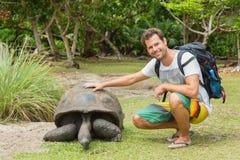 Туристское подавая Aldabra гигантские черепахи на острове Curieuse, Сейшельских островах Стоковая Фотография
