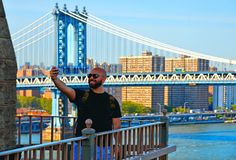 Туристское принимая selfie на Бруклинском мосте с предпосылкой моста Манхэттена на Гудзоне и горизонта архитектуры в Нью-Йорке стоковая фотография rf